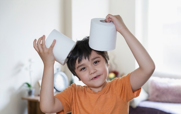 Happy young boy with smiling face playing with toilet paper