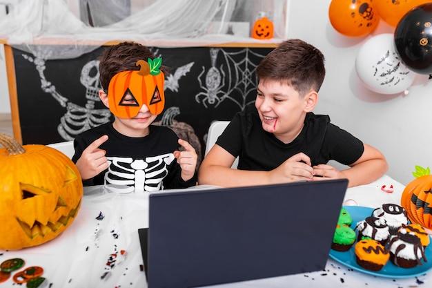 행복한 어린 소년, 할로윈 날에 노트북을 사용하는 화상 통화를 통해 조부모와 이야기하는 형제, 할로윈에 대한 그의 새로운 마스크를 보여주는 흥분된 아이