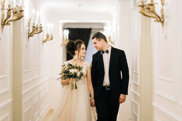 Happy young bride and groom walking down the corridor