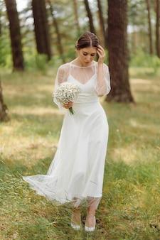 Счастливая молодая невеста в белом свадебном платье в сосновом лесу