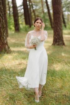 松林の白いウェディングドレスで幸せな若い花嫁