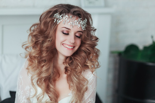Happy young bride in tiara and lingerie laughing. close portrait.