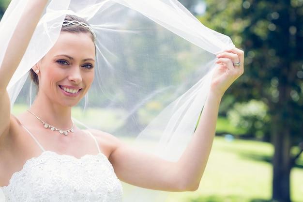 Happy young bride unveiling self in garden