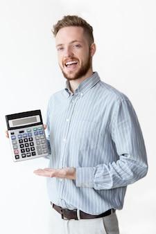 Счастливый молодой брокер, показывающий прибыль от калькулятора