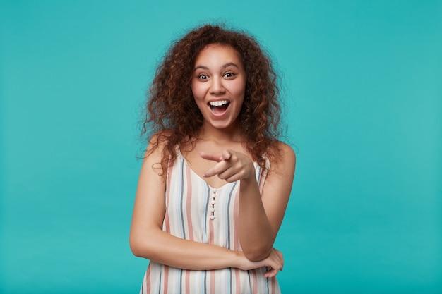 夏のブラウスで青の上に立っている間、人差し指で元気に指している自然な化粧の幸せな若い茶色の目の長い巻き毛の女性