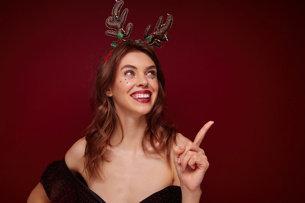 Happy young brown haired cheerful woman with festive makeup and silver stars on her face showing cheerfully upwards with forefinger, enjoying x-mas theme party