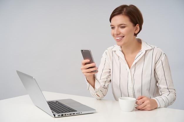 Счастливая молодая шатенка с естественным макияжем держит мобильный телефон в поднятой руке и широко улыбается, глядя на экран, позирует на белом с чашкой чая