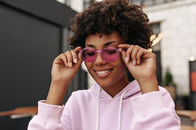 Счастливая молодая брюнетка кудрявая женщина в фиолетовой толстовке с капюшоном улыбается и надевает розовые стильные солнцезащитные очки