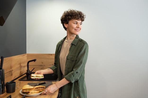 Счастливая молодая брюнетка в повседневной одежде принимает тарелку с домашними бутербродами для семьи, стоя у деревянного стола на кухне