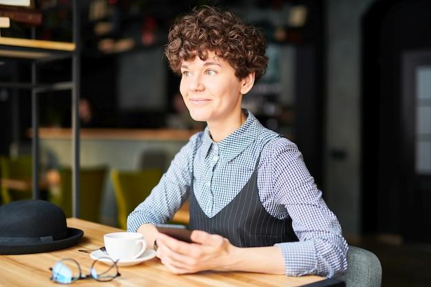 カフェのテーブルに座って、ドリンクを飲みながらスマートフォンでスクロールするスマートカジュアルウエアで幸せな若いブルネットの女性