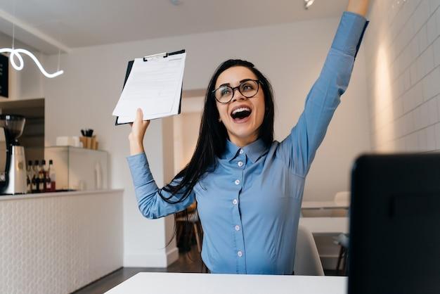 Счастливая молодая брюнетка девушка в синей рубашке и очках выучила домашнее задание