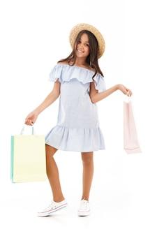 Счастливая молодая брюнетка девушка в платье и соломенной шляпе позирует с пакетами на белом