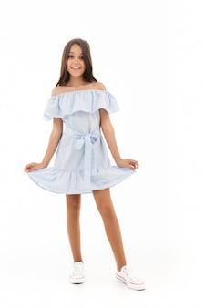 Счастливая молодая брюнетка девушка в платье позирует на белом