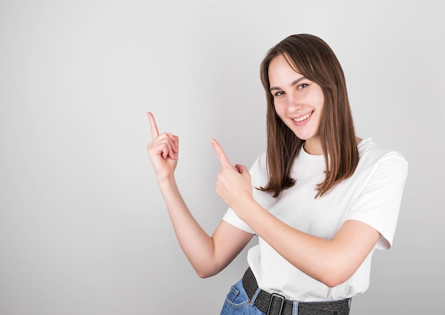 Happy young brunette girl in white t-shirt and jeans pointing to the side with two fingers and smiling while standing on gray background