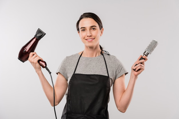 Happy young brunette hairdresser in apron holding hairdryer and hairbrush while standing in front of camera in isolation