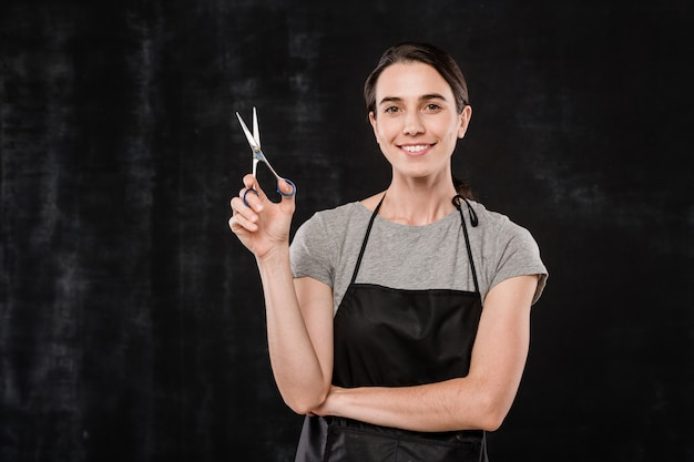 Happy young brunette hairdresser in apron holding scissors while standing in front of camera against black background