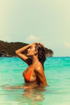 海に立っているオレンジ色のビキニで幸せな若いブルネット。夏休みのコンセプト。
