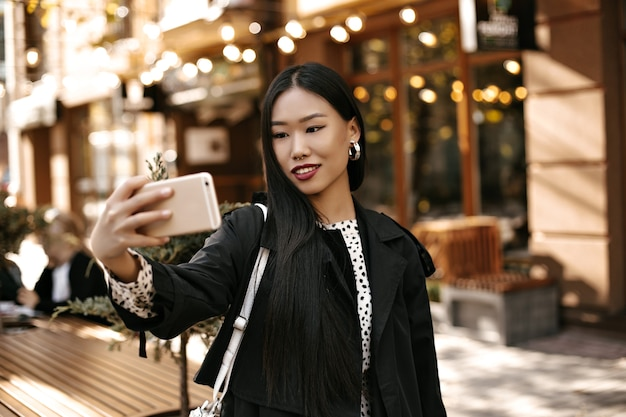 Happy young brunette lady in stylish black trench coat smiles sincerely, holds phone and takes selfie outside near street cafe