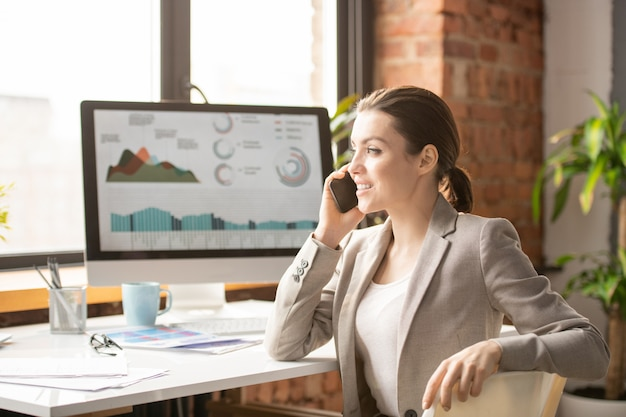 Happy young brunette office manager consuting client on smartphone while sitting by desk and looking through window