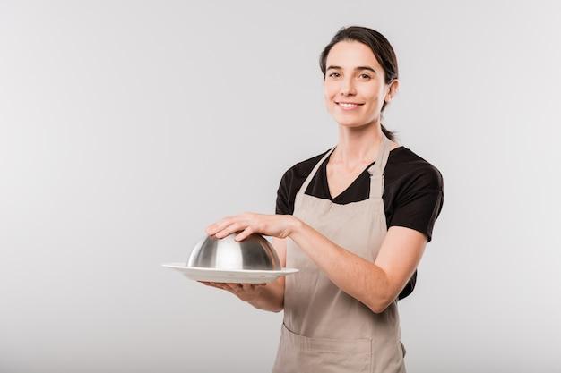 Счастливая молодая брюнетка официантка в фартуке, держащая руку на обложке cloche, стоя перед камерой в изоляции