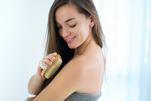 Happy young brunette woman brushing skin with a dry wooden brush to prevent and treatment body problem after shower at home. skin health