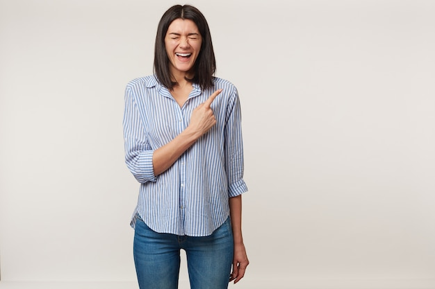 Happy young brunette woman closed eyes and loudly laughing, pointing with index finger to the rightside on blank copy space, dressed in striped shirt, isolated
