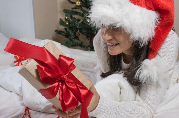 サンタクロースの帽子をかぶった幸せな若いブルネットの女性は、白いベッドの上に横たわってクリスマスのギフトボックスを開きます