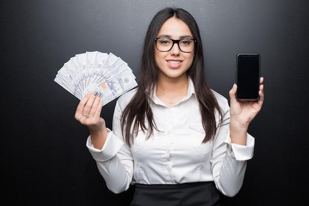 空白の画面と黒い壁で隔離の手で現金お金でスマートフォンを示す白いシャツの幸せな若いブルネットの女性