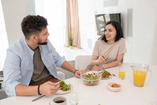 테이블 옆에서 직접 만든 야채 샐러드와 오렌지 주스를 먹으면서 남편을 미소로 바라보는 행복한 젊은 브루네트 여성