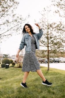 デニム ジャケットと公園を歩いているドレスを着た幸せな若いブルネットの女性