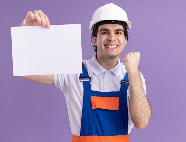 Felice giovane costruttore uomo in costruzione uniforme e casco di sicurezza tenendo la pagina vuota guardando davanti con il sorriso sul viso stringendo il pugno in piedi sopra la parete viola