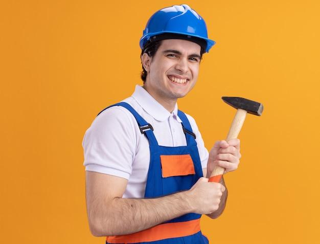 Felice giovane costruttore in uniforme da costruzione e casco di sicurezza che tiene il martello guardando la parte anteriore sorridente allegramente in piedi sopra la parete arancione