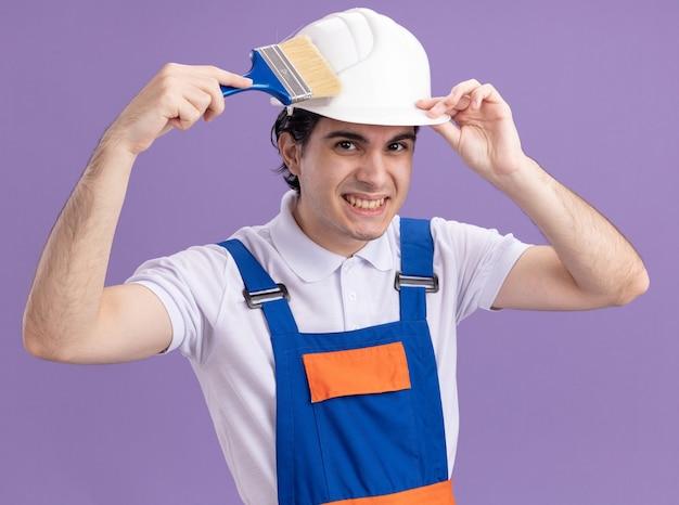 Felice giovane costruttore in uniforme da costruzione e casco di sicurezza che tiene il pennello guardando davanti sorridente in piedi sopra la parete viola