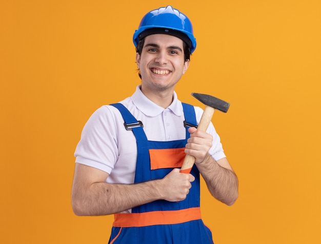 건설 유니폼 및 안전 헬멧에 행복 한 젊은 작성기 남자 오렌지 벽 위에 유쾌 하 게 서 웃 고 전면을보고 망치를 들고