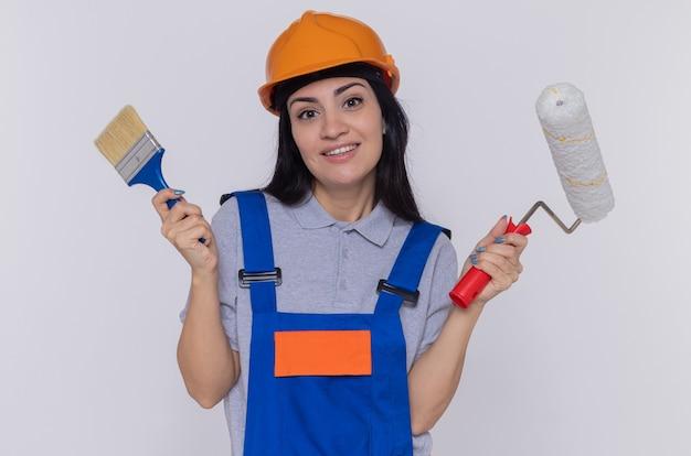 Felice giovane donna costruttore in uniforme da costruzione e casco di sicurezza che tiene pennello e rullo di vernice guardando samiling anteriore fiducioso in piedi sopra il muro bianco