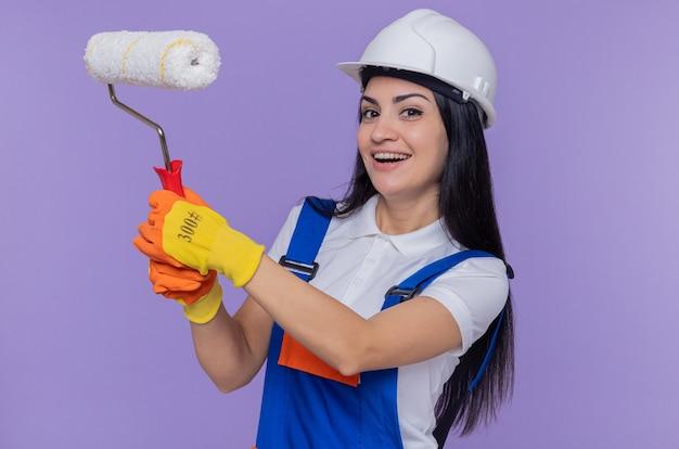 Felice giovane builder donna in costruzione uniforme e casco di sicurezza che indossa guanti di gomma tenendo il rullo di vernice guardando la parte anteriore sorridente allegramente in piedi sopra la parete viola