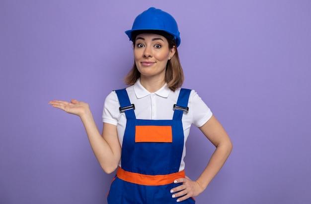 紫色の壁の上に立っている彼女の手の腕でコピースペースを提示して自信を持って笑顔の正面を見て建設制服と安全ヘルメットの幸せな若いビルダーの女性