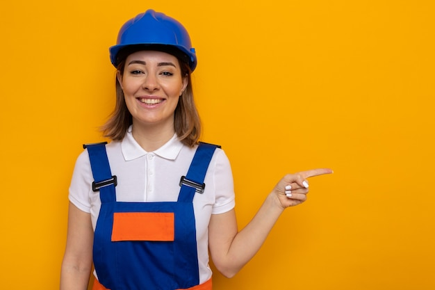 建設制服と安全ヘルメットの幸せな若いビルダーの女性は、人差し指を横に向けて元気に笑顔を見て
