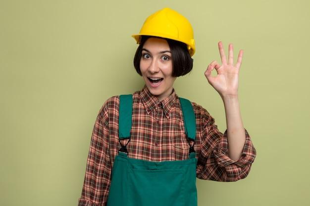 건설 유니폼과 안전 헬멧을 쓴 행복한 젊은 건축업자 여성이 녹색 위에 서 있는 확인 사인을 하며 즐겁게 웃고 있다