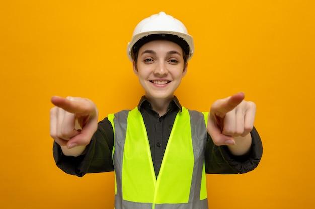 オレンジ色の上に立っている人差し指で自信を持って指している建設ベストと安全ヘルメットの幸せな若いビルダーの女性