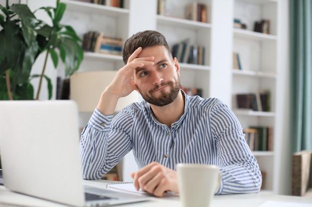 幸せな若いビジネスマンは、自己隔離中に自宅から財務書類を分析しています。