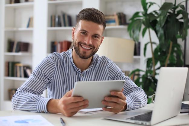 행복한 젊은 사업가가 자가 격리 동안 집에서 재정 문서를 분석하고 있습니다.