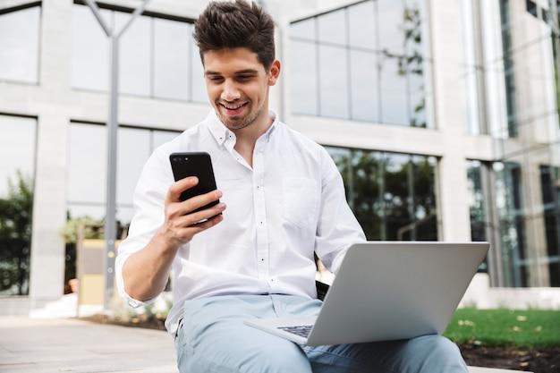 携帯電話を使用して幸せな若いビジネスマン