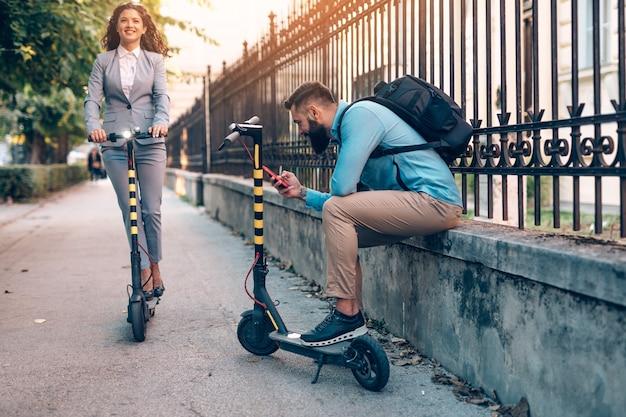 도시 거리에서 전기 스쿠터를 타면서 함께 즐기는 행복한 젊은 비즈니스 파트너.