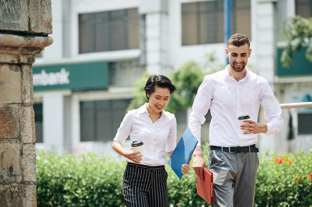 Happy young business people walking in the street