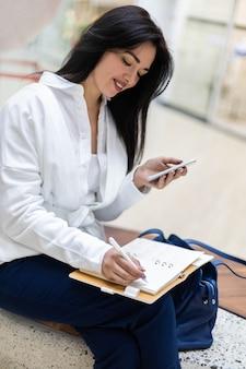 현대 쇼핑 센터 홀에 앉아 스마트폰을 사용하여 채팅하는 행복한 젊은 비즈니스 여성