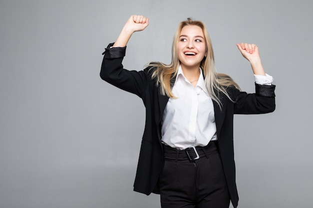 Happy young business woman doing winner gesture, keeping eyes closed posing isolated