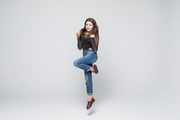 Счастливая молодая бизнес-леди изолированная на белой стене.