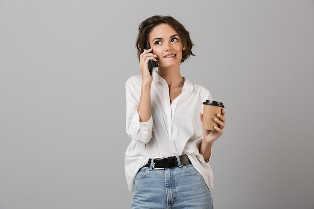 Happy young business woman posing isolated over grey wall talking by mobile phone drinking coffee