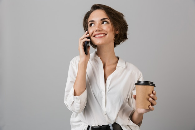 Happy young business woman posing isolated over grey wall talking by mobile phone and drinking coffee